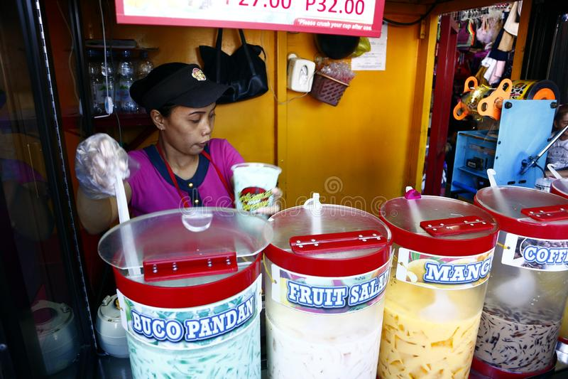 A woman sells assorted fruit juice and other refreshments during a hot summer day. ANTIPOLO CITY, PHILIPPINES – JUNE 18, 2019: A woman sells assorted royalty free stock photos