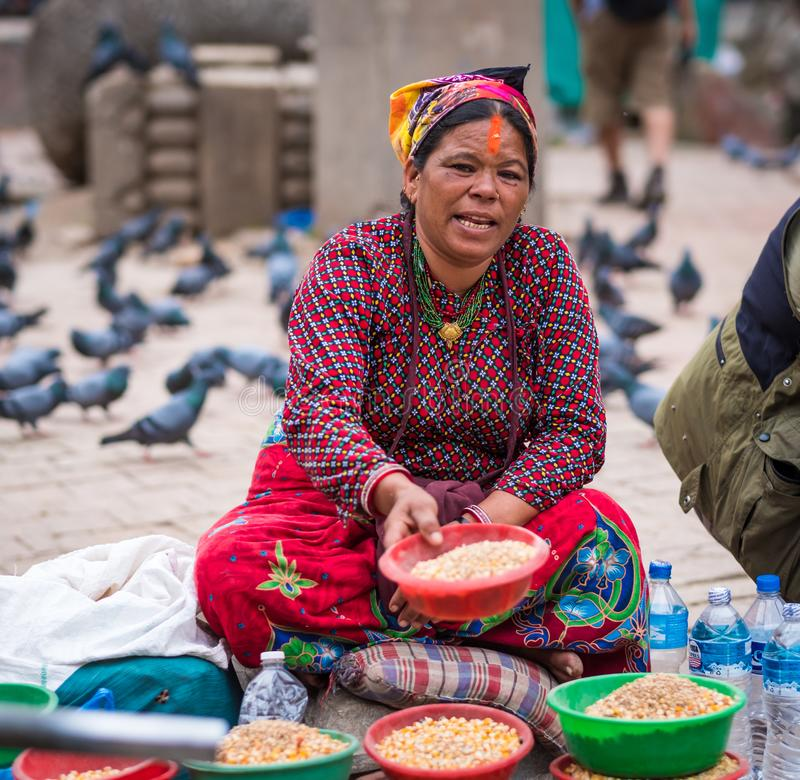 Woman sells corn seeds on Nepalese street market. Kathmandu, Nepal - 06 October 2017: Woman in traditional clothes sells corn seeds on Nepalese street market stock photos