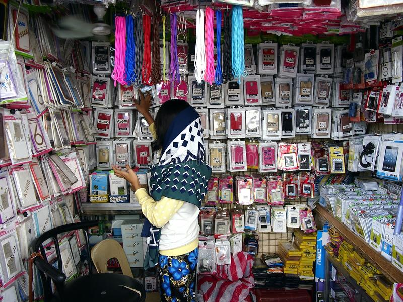 A woman sells a wide variety of smartphone and accessories in her store. stock images