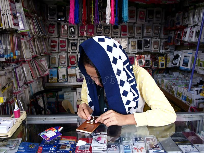 A woman sells a wide variety of smartphone and accessories in her store. royalty free stock photo