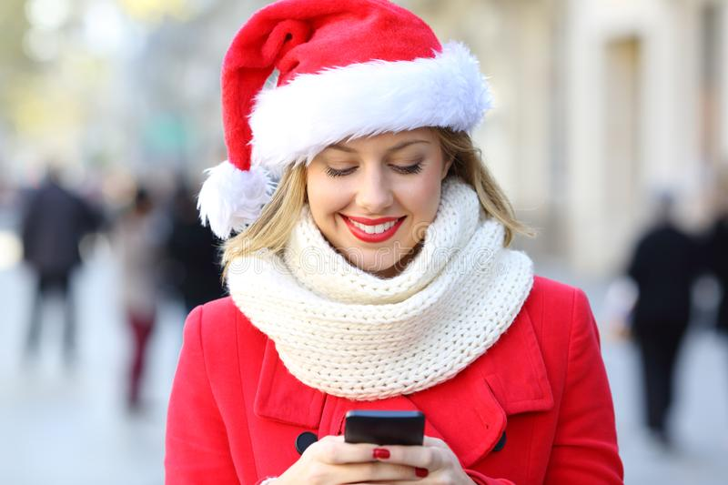 Woman sending phone text on christmas in the street. Front view of a happy woman sending phone text on christmas in the street stock photography