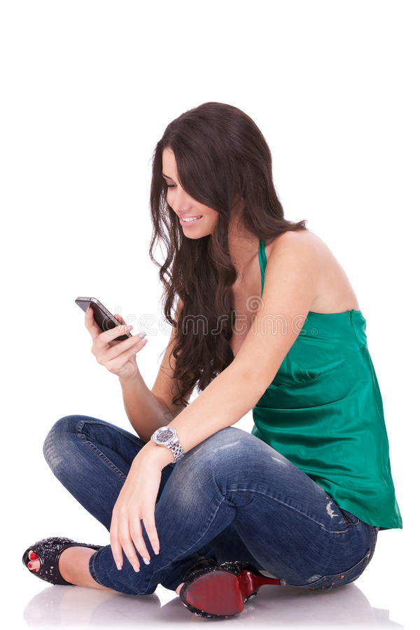 Woman sending an sms. Portrait of a beautiful woman seated on white background, sending an sms stock image
