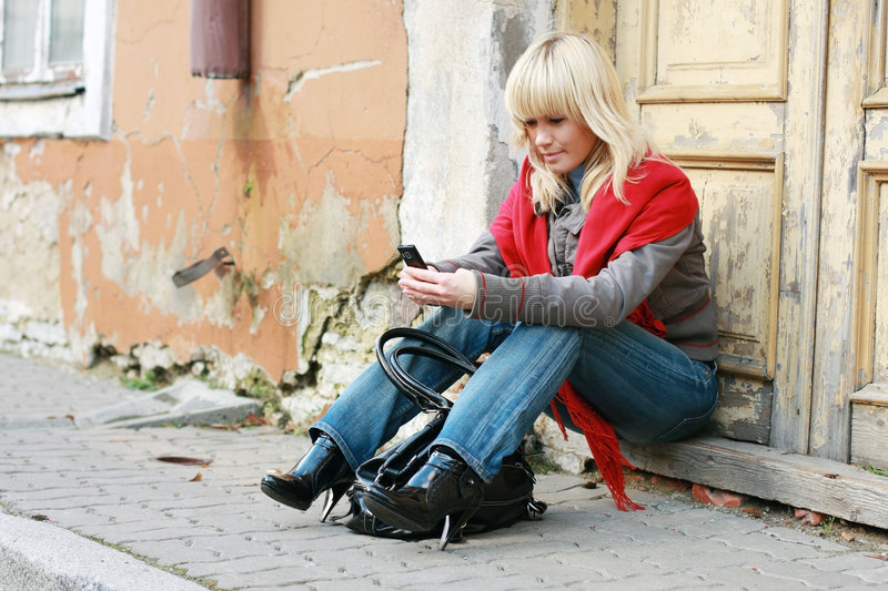 Woman sending sms. Young woman sitting in the street and sending sms royalty free stock image