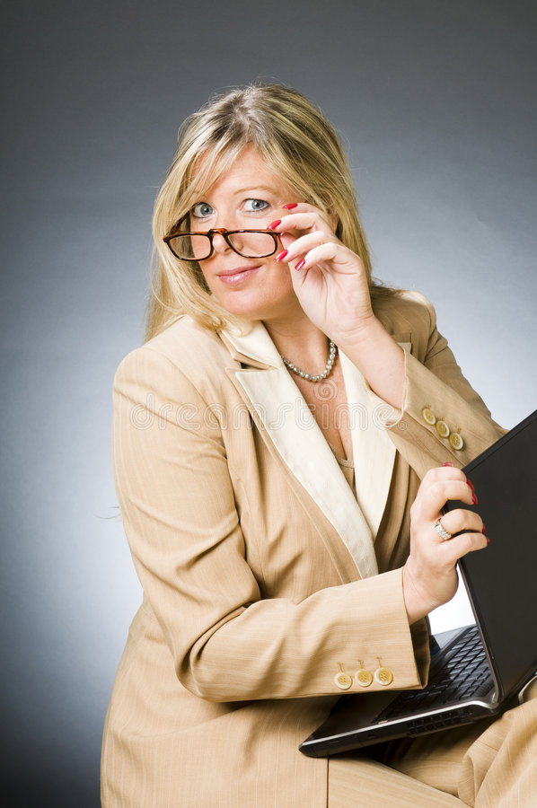 Woman senior business executive. Pretty beautiful middle age blond woman inquisitive look expression senior business executive manager corporation with laptop stock photos