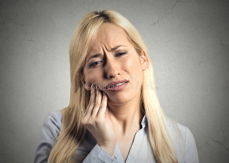 Woman with sensitive tooth ache. Closeup portrait young woman with sensitive tooth ache crown problem about to cry from pain touching outside mouth with hand royalty free stock photos