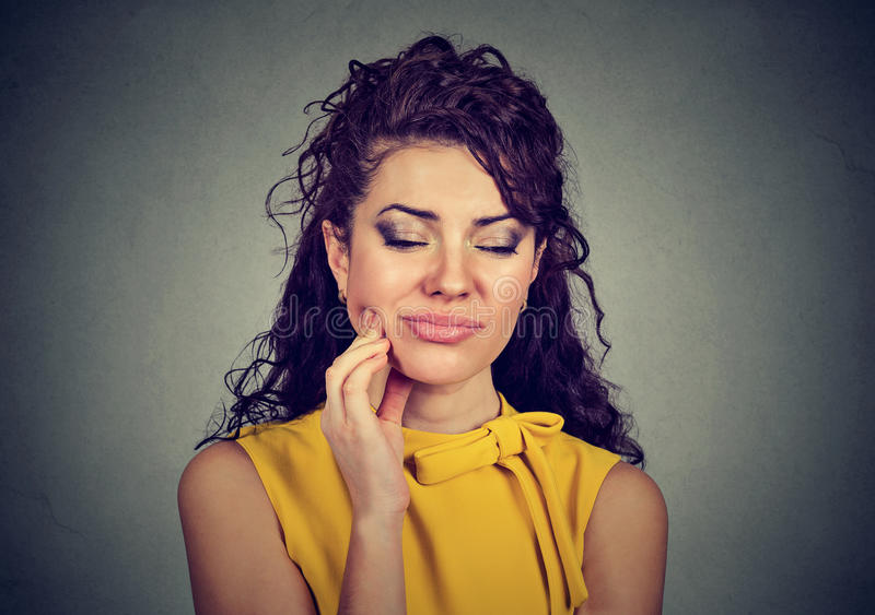 Woman with sensitive tooth ache crown problem about to cry from pain. Touching outside mouth with hand isolated gray background stock photos