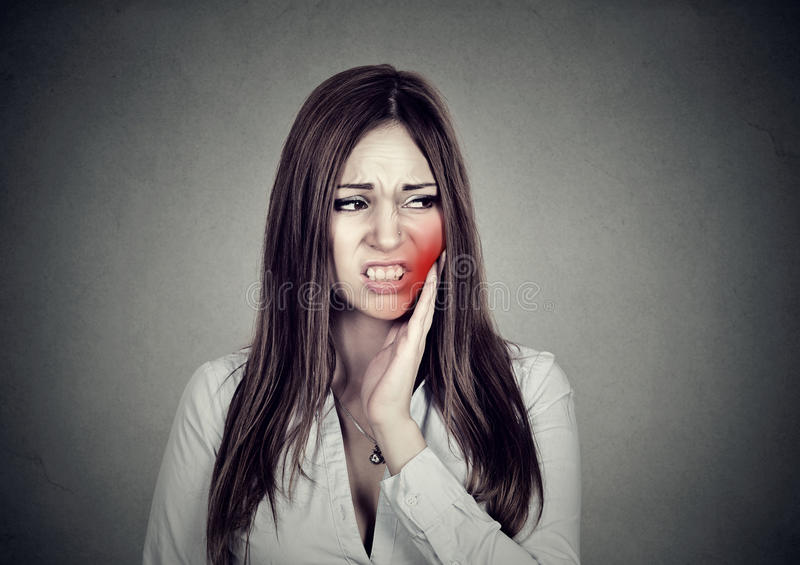 Woman with sensitive toothache suffering from pain touching outside mouth. Young woman with sensitive toothache crown problem suffering from pain touching royalty free stock images
