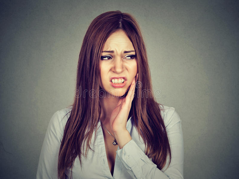 Woman with sensitive toothache about to cry from pain. Closeup portrait woman with sensitive toothache crown problem about to cry from pain touching outside royalty free stock photo