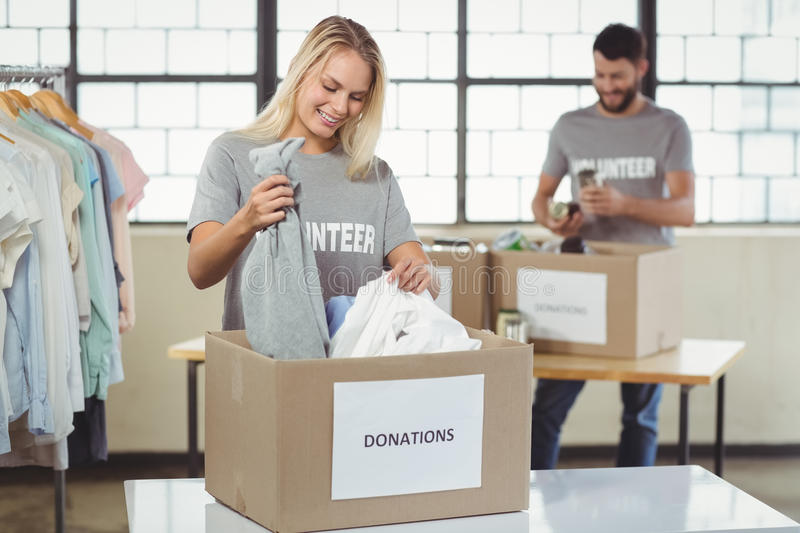 Woman separating clothes from donation box. In office stock image