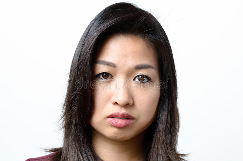 Woman with serious blank stare. One beautiful young woman with stray hair and serious expression and blank stare royalty free stock images