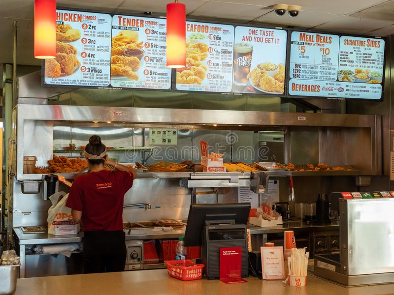 Woman serving chicken from heat lamp tray behind counter at Popeyes Fried Chicken location. Berkeley, CA OCTOBER 6, 2018: Woman serving chicken from heat lamp stock image