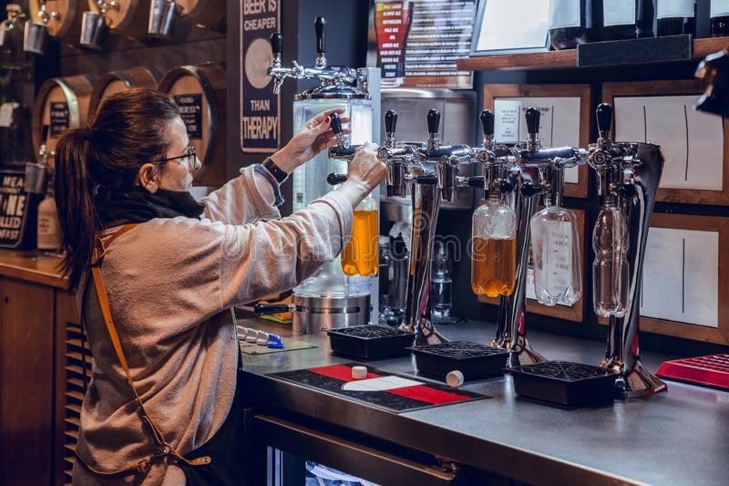 Woman serving craft beer in bulk in store stock photos