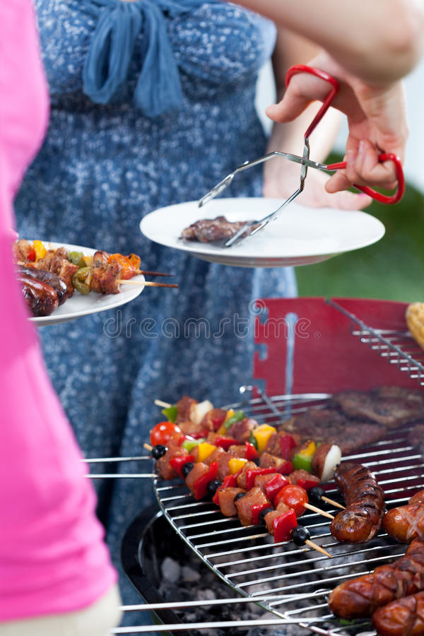 Woman serving dinner on barbecue party stock image