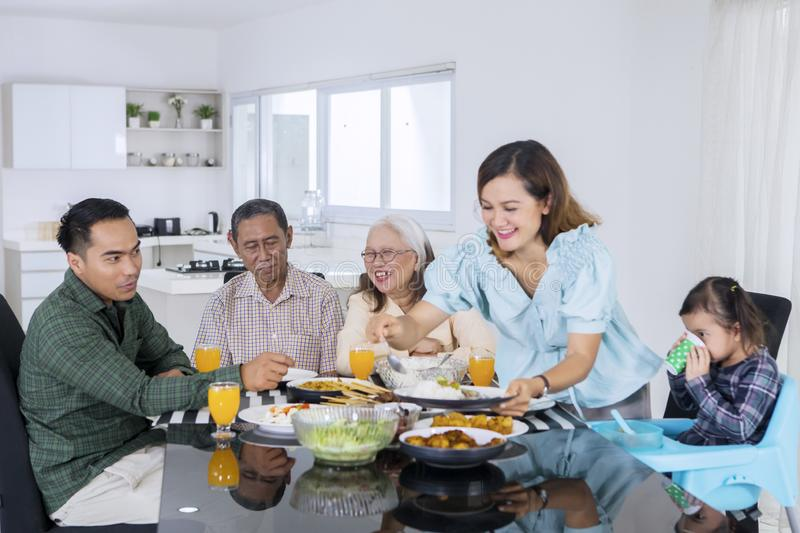 Woman serving food for her multi generation family royalty free stock photography