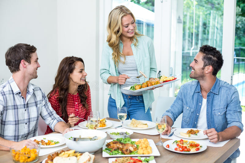 Woman serving food to friends stock photo