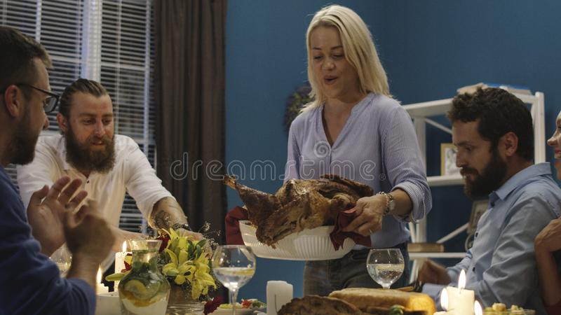 Woman serving holiday turkey on dinner with friends royalty free stock photo