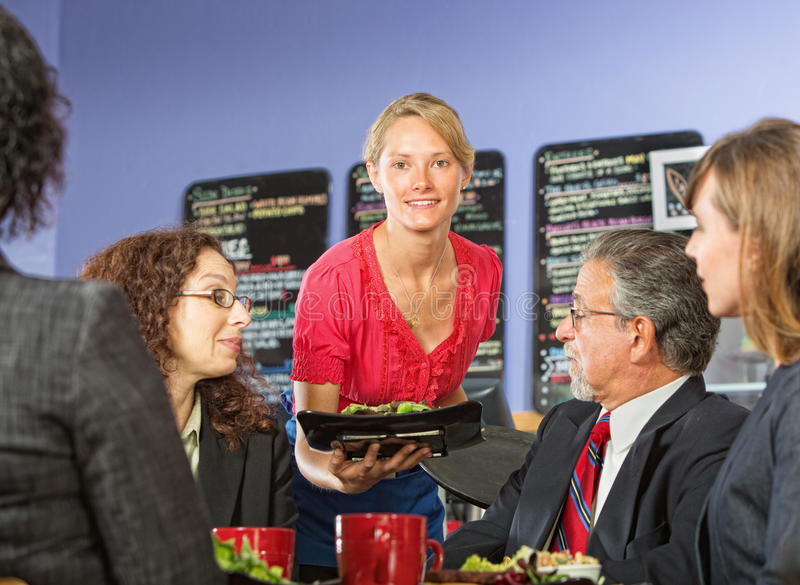 Woman Serving Lunch. Pretty young server bringing food to group of business people royalty free stock photography