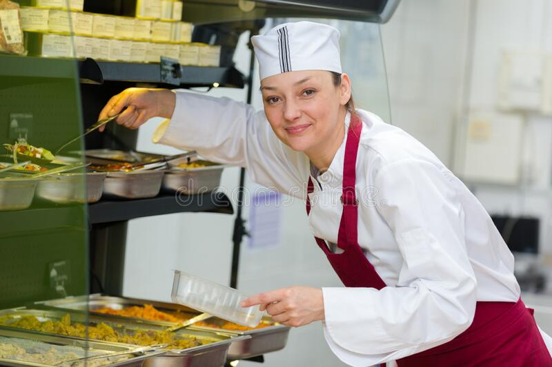 Woman serving at takeaway buffet counter stock images