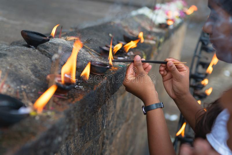 Woman sets fire to fragrant sticks in the temple offerings place. DAMBULLA, SRI LANKA - 22 NOV 2016: Woman sets fire to fragrant sticks in the temple offerings royalty free stock image