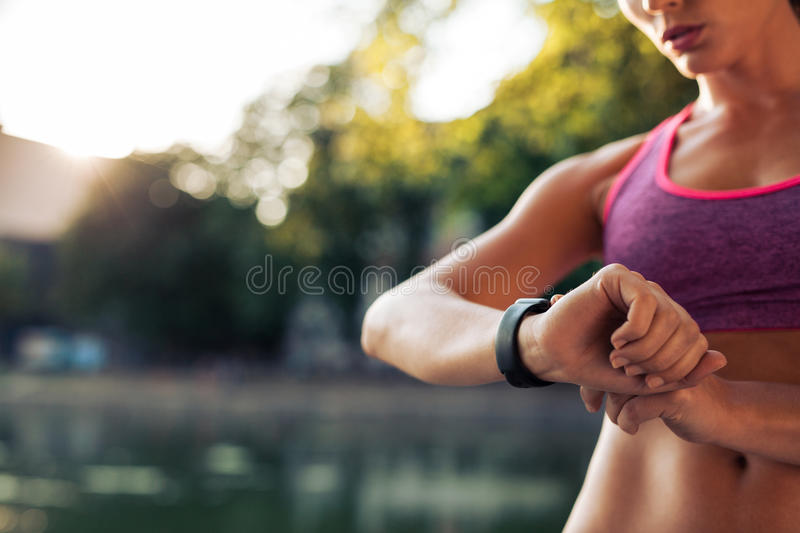 Woman setting up the smartwatch for running stock photography
