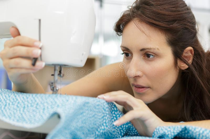 Woman sewing with sewing machine in workshop stock photos