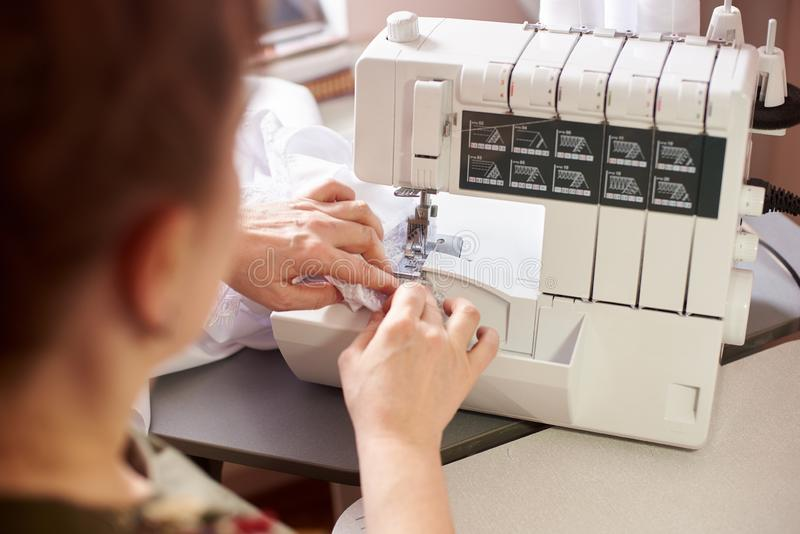 Woman in sewing studio: sewing with serger, overlocker. Fashion designers atelier. Close up view of sewing machine. stock photo