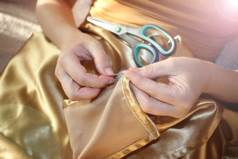 Woman sews a hole in clothes with a needle and thread. Woman`s hands with needle close up. Ancient craft. toned stock photo