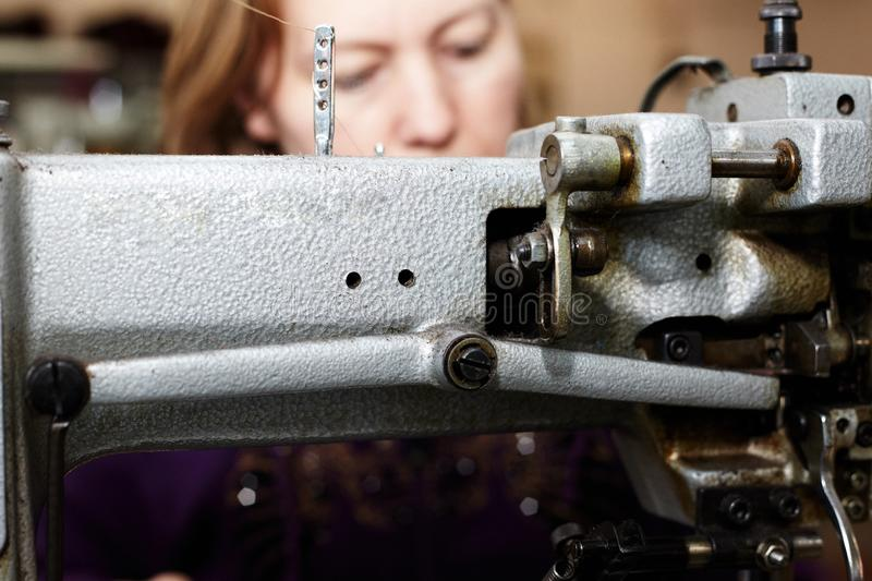 A woman sews a leather strip with a special sewing machine for leather, used in the production of handbags / shoes. A woman sews a leather strip with a special royalty free stock photography