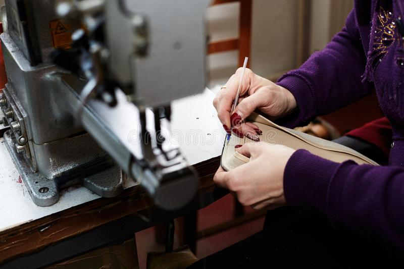 A woman sews a leather strip with a special sewing machine for leather, used in the production of handbags / shoes. A woman sews a leather strip with a special royalty free stock photos