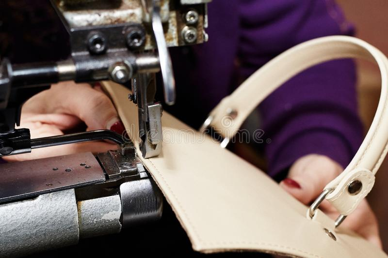 A woman sews a leather strip with a special sewing machine for leather, used in the production of handbags / shoes. A woman sews a leather strip with a special royalty free stock image