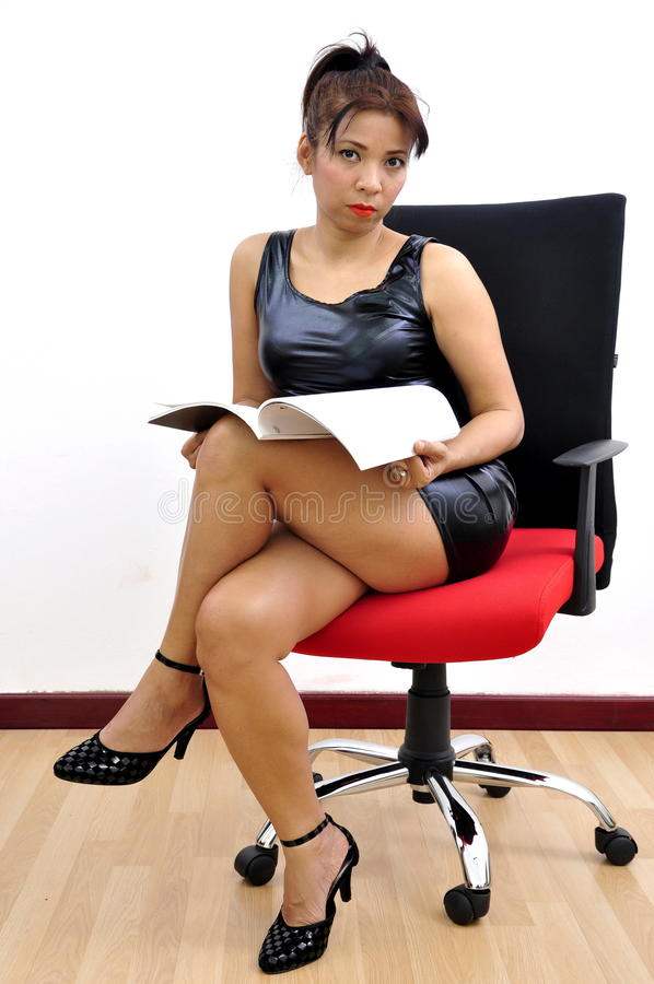 Woman black dress legs crossed reads document stock images