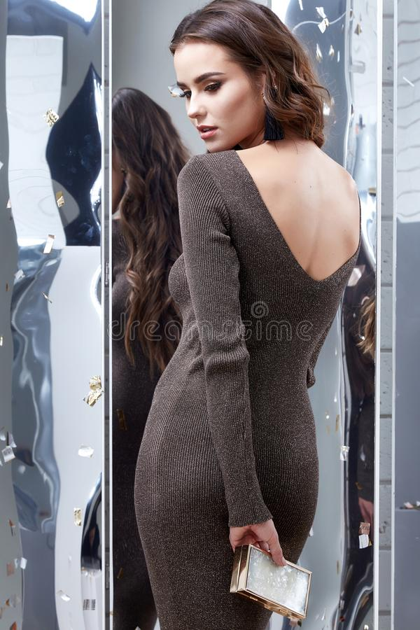 Woman brunette curly hair bright evening makeup beauty face. Wear luxury clothes elegant skinny brown dress style party holiday celebrate New Year mirror shiny stock images