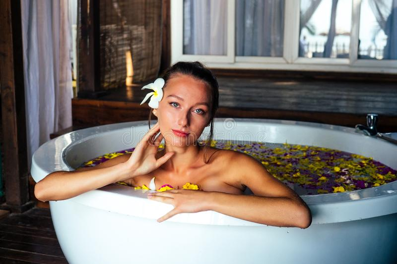 Woman sexy brunette relaxing in bath with tropical flowers outdoor at luxury hotel resort. Organic skin health care. Beautiful girl resting in hotel spa royalty free stock photo