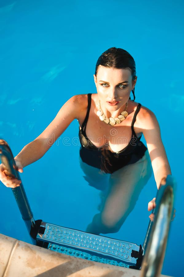 Woman With Fit Body In Fashion Bikini, Swimwear Coming Out From Swimming Pool Water.  stock photography