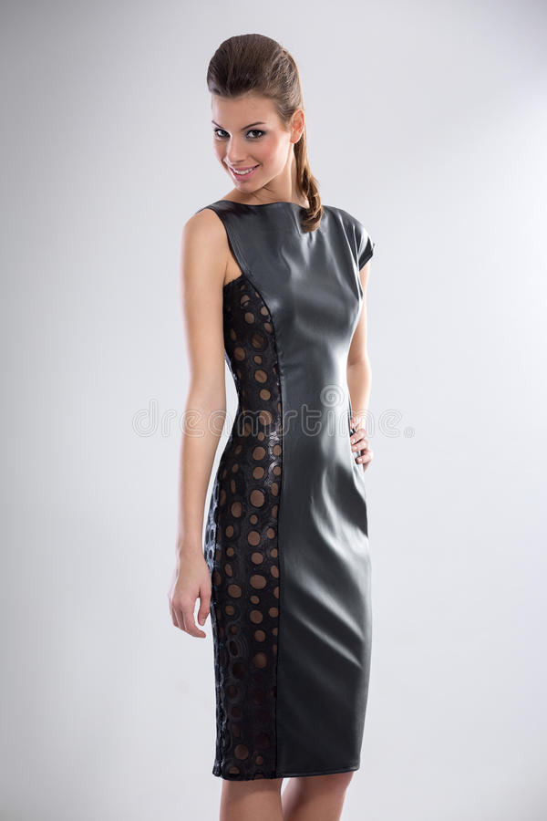 Woman in leather dress. Young woman in black, leather dress royalty free stock images