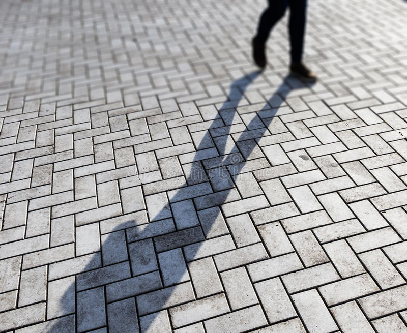 Woman and shadow. Woman walking, her shadow on detailed ground with blur effect royalty free stock image