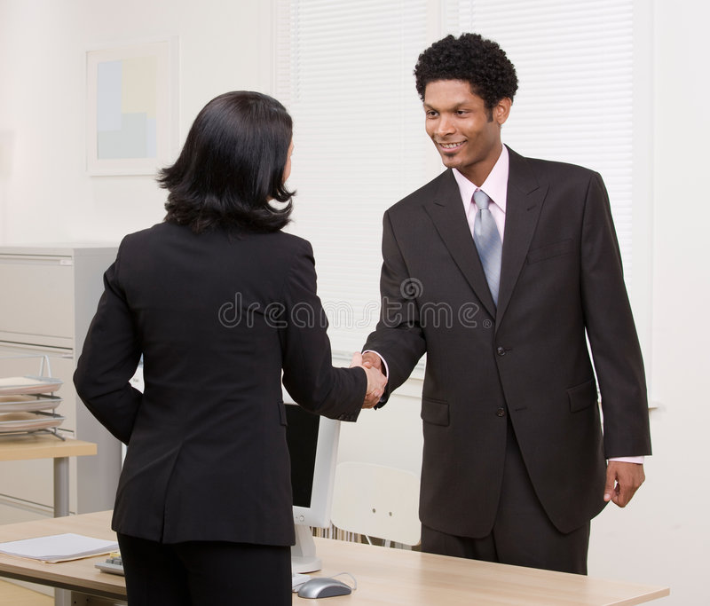 Woman shaking hands with co-worker at desk stock photos
