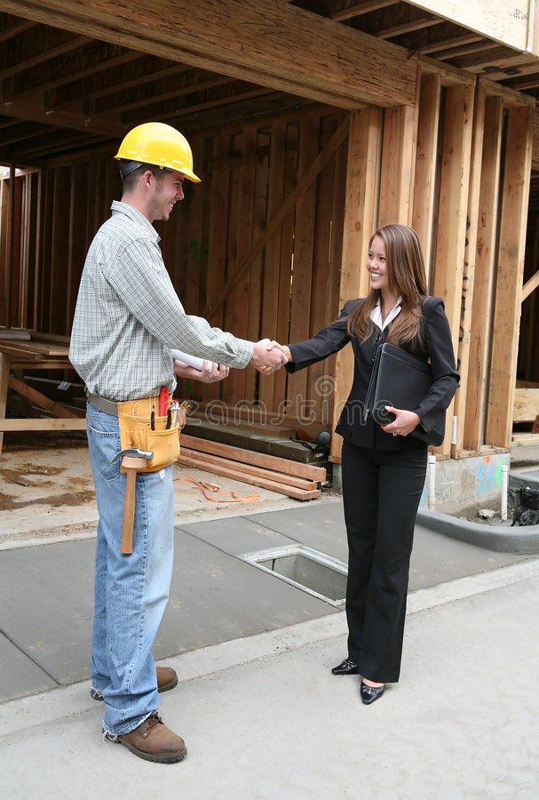 Woman Shaking Hands with Construction Man royalty free stock photos