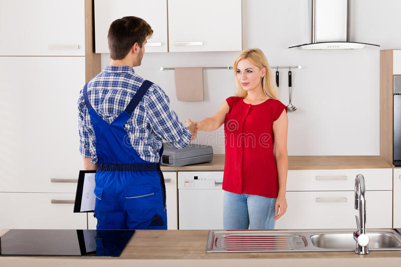 Woman Shaking Hands With Male Plumber royalty free stock photography