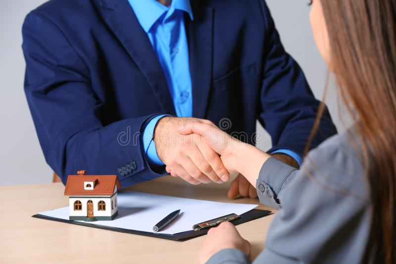 Woman shaking hands with real estate agent at table in office. Home insurance stock photography