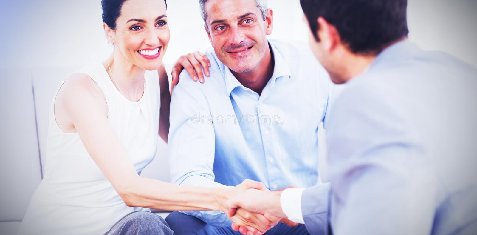 Woman shaking hands with salesman sitting beside husband. On couch at home royalty free stock photos
