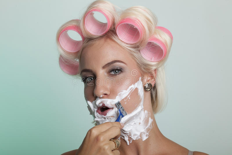 Woman shaving her face stock photography