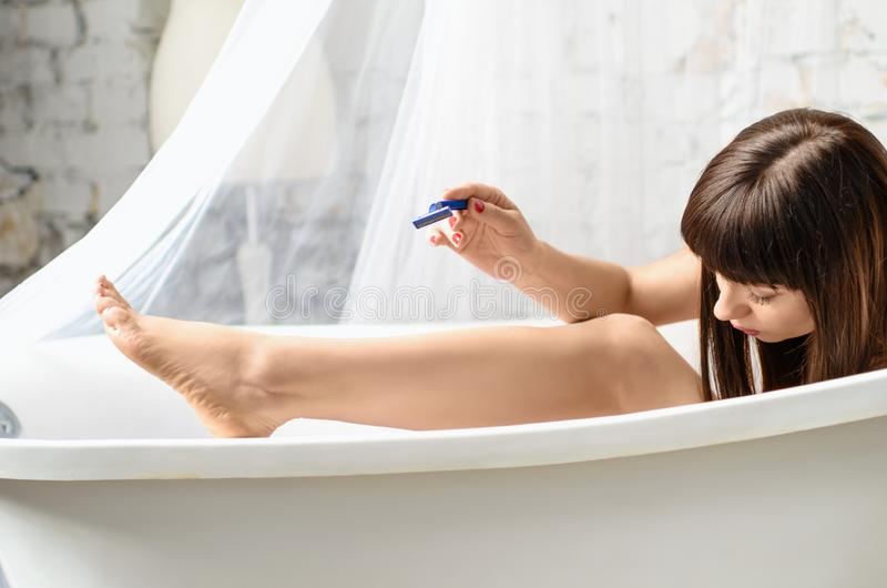 Woman shaving legs with razor blade in bath. Hair removal. Skin damage, scratch royalty free stock images