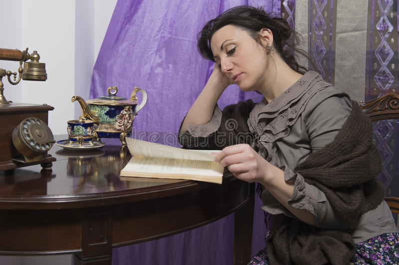 Woman with shawl intent on reading stock photos