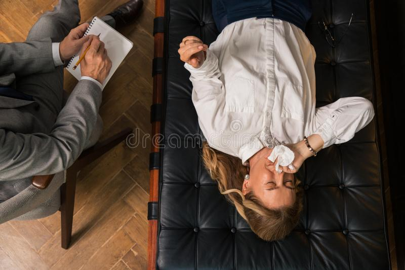Woman shedding tears in the presence of her doctor royalty free stock image