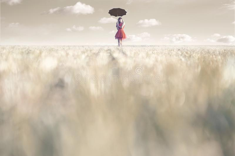 Woman shelters from the sun with her umbrella in a surreal place. Woman shelters from the sun with her umbrella stock images