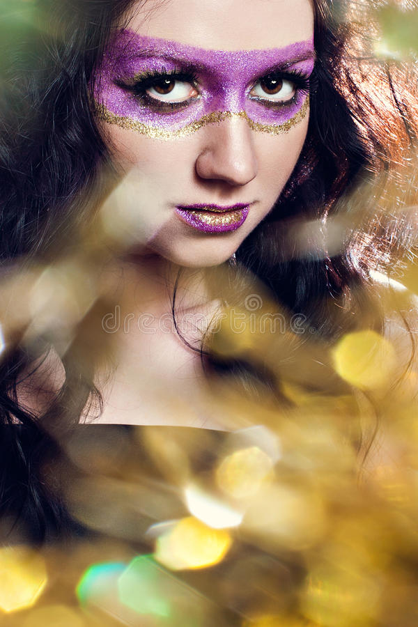 Woman with shiny extreme violet-gold make-up stock photos