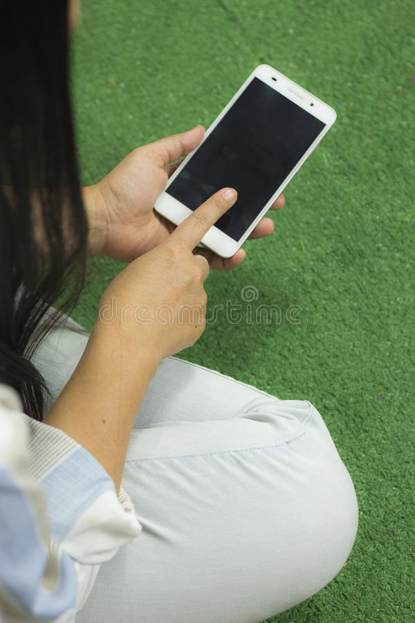 Woman in shirt playing on phone, sitting on a green floor with legs crossed stock image