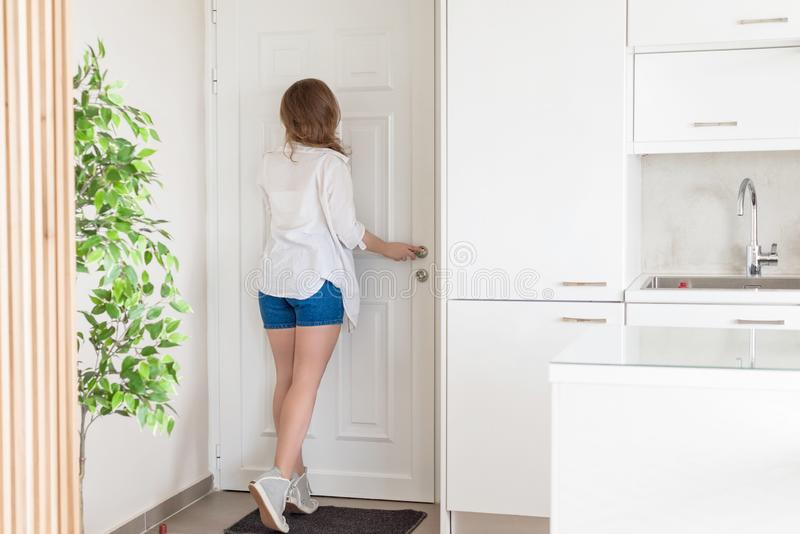 Woman in shirt and shorts looking in peephole door when somebody rings the doorbell.  stock photography