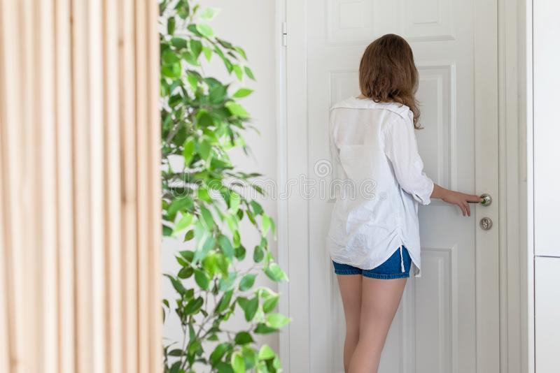 Woman in shirt and shorts looking in peephole door when somebody rings the doorbell.  stock images